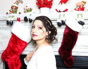 Monica Ortiz by a holiday fireplace