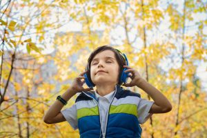 Young boy in a forest with headphones